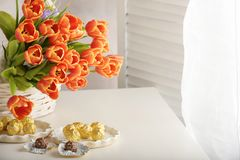 Candy in white dishes and a bouquet of orange tulips on light dyed wooden surface. Horizontal royalty free stock image