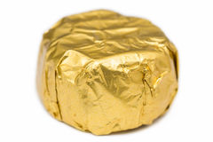 Candy Wrapped In Golden Foil. Candy In Golden Foil On A White Background royalty free stock images