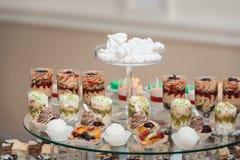 Candybar en un restaurante Tonto blanco adornado de la tabla de los pasteles dulces Fotografía de archivo libre de regalías