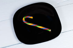 Candycane. Bright striped candy on a black plate Royalty Free Stock Photos