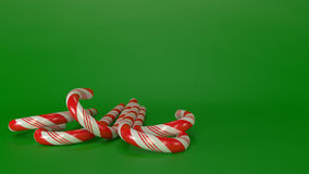Candycanes with green background. Red and White candycanes in front view with green background. Christmas decoration.No shadow. 3d generated royalty free stock photo
