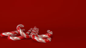 Candycanes with red background. Red and White candycanes in front view with read background. Christmas decoration.No shadow. 3d generated Stock Photos