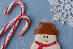 Candycanes, Snowman Cookie and Snowflake on Light Blue Wood Back Stock Photo