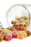 Candys colorido fora de um frasco de vidro Fotos de Stock Royalty Free