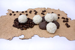 Candys and grains of coffee on a singed paper. Isolated candys and grains of coffee on a singed paper on a white background Royalty Free Stock Photography