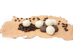 Candys and grains of coffee on a singed paper Stock Photos