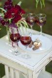 Candys och exponeringsglas för chokladtryfflar med rött vin på vit uppvaktar Royaltyfri Bild