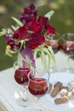 Candys och exponeringsglas för chokladtryfflar med rött vin på vit uppvaktar Arkivfoto