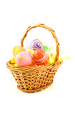 Cane basket with colorful easter eggs Stock Photos