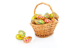 Cane basket with colorful easter eggs Stock Images