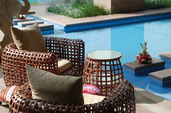 Cane chairs beside pool Royalty Free Stock Photo