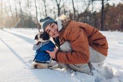 Cane del carlino che cammina sulla neve con il suo padrone Cappotto d'uso di inverno del cucciolo Uomo che abbraccia il suo anima immagini stock