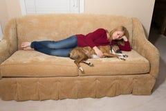 Cane di coccole della donna sullo strato - il cane è addormentato immagine stock libera da diritti