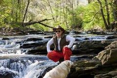 cane di distanza che osserva il fiume dell'uomo a fotografia stock
