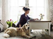 Cane di golden retriever di coccole della donna a casa immagine stock libera da diritti