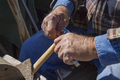 Cane Maker. Detail photo of man's hands with pocket knife and wood royalty free stock photo