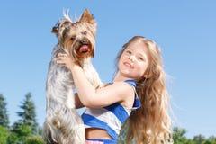 Cane sorridente della tenuta della bambina Immagini Stock