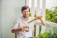 Cane sugar concept. The man jokingly eating sugar cane and drinks tea Stock Photography