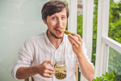 Cane sugar concept. The man jokingly eating sugar cane and drinks tea Royalty Free Stock Images