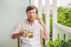 Cane sugar concept. The man jokingly eating sugar cane and drinks tea Stock Image