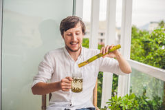 Cane sugar concept. The man jokingly eating sugar cane and drinks tea Stock Photo