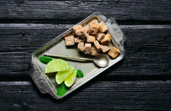 Cane sugar with lime and mint leaves in a tray on the old wooden Stock Photography