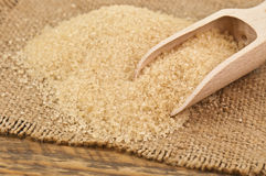 Cane sugar. Sweet cane sugar on burlap with wooden spoon Royalty Free Stock Photography