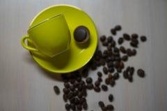 Caneca amarela com uma morango e gr?es do caf? imagem de stock