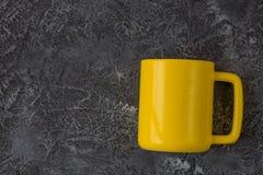 Caneca amarela na tabela de pedra escura com espa?o da c?pia imagens de stock royalty free