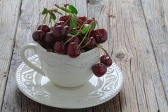 Caneca branca com as cerejas maduras no fundo de madeira velho Foto de Stock