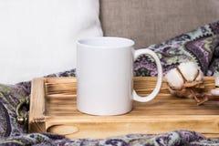 Caneca branca em uma bandeja de madeira, o modelo Decorações acolhedores da casa, do linho e das lãs Imagens de Stock