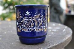 A caneca cerâmica azul do Natal com uma imagem está na tabela de madeira Imagens de Stock