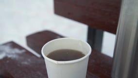 A caneca com chá está no banco no inverno video estoque