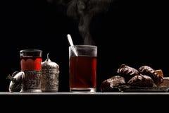 Caneca com chá quente de que há vapor, em um fundo escuro com marshmallows e doce fotografia de stock