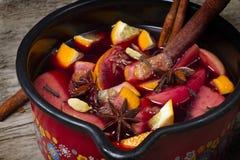 Caneca com vinho ferventado com especiarias na tabela de madeira Imagem de Stock