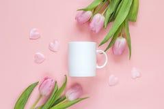 A caneca de café branco com tulipas cor-de-rosa e ona dos corações pica o fundo Foto de Stock