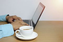 caneca de café branco no portátil de madeira marrom do assoalho e do computador do Ha fotos de stock royalty free