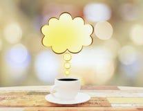 Caneca de café com o speachbubble amarelo na tabela de madeira Foto de Stock