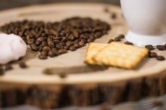 Caneca de café dos feijões de café em um corte de madeira Fotografia de Stock