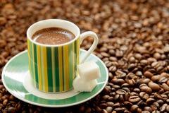 A caneca de café e de açúcar fortes dispersou em feijões de café Foto de Stock Royalty Free