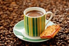 A caneca de café e de biscoitos fortes dispersou em feijões de café Imagem de Stock