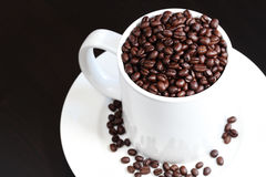 A caneca de café encheu-se com os feijões de café frescos Fotografia de Stock Royalty Free