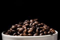 A caneca de café encheu-se com os feijões de café sobre o fundo preto Imagens de Stock