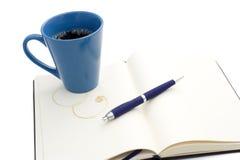 Caneca de café no caderno Foto de Stock Royalty Free