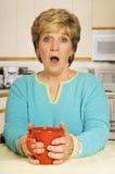 Caneca de café surpreendida da terra arrendada da mulher na cozinha Foto de Stock