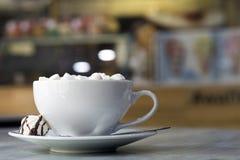 Caneca de caf? com os marshmallows na placa da porcelana no fundo interior colorido borrado do bokeh foto de stock royalty free