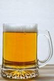 Caneca de cerveja clara fresca na madeira Imagens de Stock Royalty Free