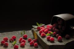 Caneca de framboesas maduras no fundo preto foto de stock