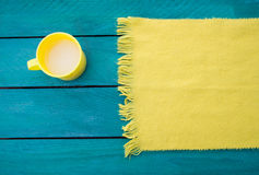 A caneca de leite e o lenço amarelo em uma turquesa surgem Imagens de Stock Royalty Free