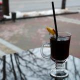 Caneca de vidro com chá marrom, saboroso, quente, perfumado, preto com uma fatia de limão e uma palha na tabela em um café na noi imagens de stock